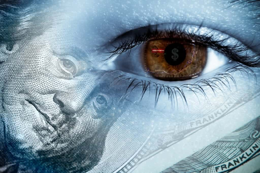Close up of an eye with a picture of Benjamin Franklin on a dollar bill superimposed over it.