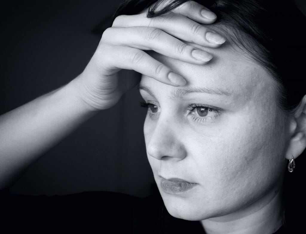 Black and white picture of a depressed woman holding her head.