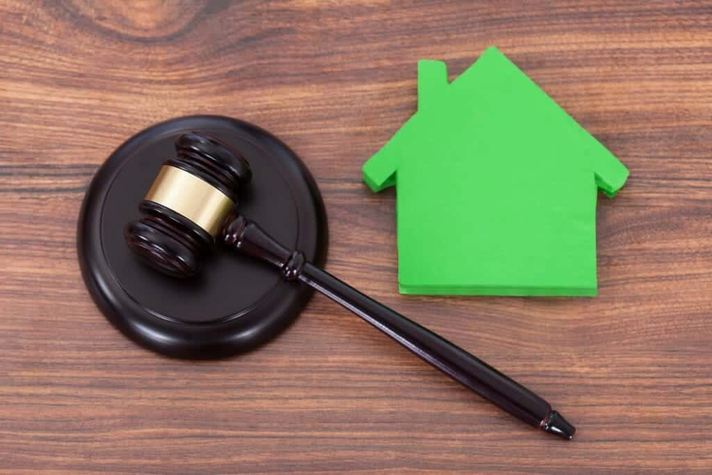 Judge's gavel next to a green cut-out of a house.