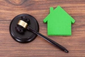 Judge's gavel next to a green cut-out of a house.Who Gets the House in a Divorce?