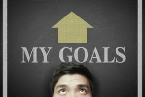 "Head of a man standing in front of a blackboard with the words ""My Goals"" and an arrow pointing up on top of his head."
