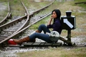 Young woman sitting next to intersection of train tracks.