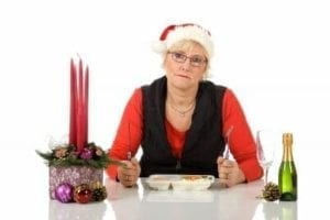Lonely woman in a Santa hat eating Christmas dinner alone - divorce during the holidays