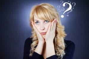 Perplexed woman holding her face with a question mark above her head.