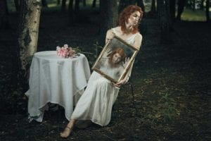 Young woman in a white dress in the forest holds a picture of herself trying to get out of the picture frame