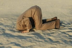 Business man kneeling down in the desert. Burying your head in the sand is not a good strategy.