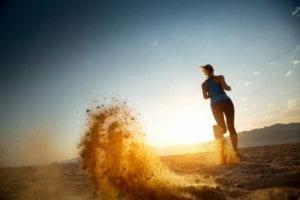 Woman running in the sunrise in the desert. Coping with divorce through exercise.