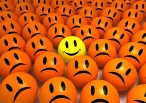 One yellow happy smiling emoticon in the middle of a crowd of orange sad emoticons
