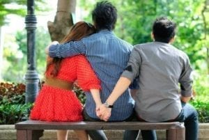 Couple on a park bench with the woman holding hands with another guy behind her husband's back.
