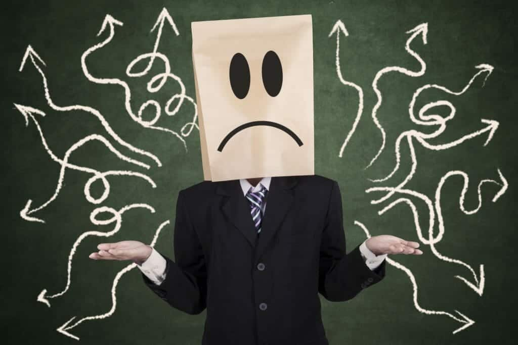 Person with bag over head and a confused face standing in front of a chalkboard with arrows on it pointing every which way.
