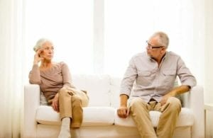 Senior couple, aggravated with each other, sitting on a couch. Grey Divorce.