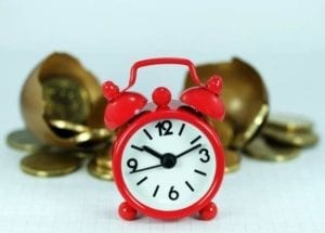 Red alarm clock in front of gold coins: save time and money