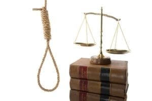 Noose hanging next to a stack of law books with the scales of justice on top.