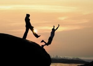 Silhouette of woman kicking man off a boulder into a river at sunset.