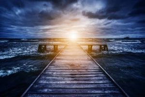 A dock in stormy waters, with the sun rising in the distance