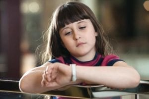 Sad little girl looking at her watch. Make time for your kids!