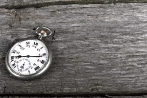 Vintage pocket watch on old wood shows passage of time.