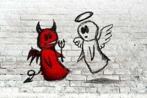 White angel and red devil drawn on a brick wall.