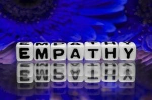 Empathy spelled out on dice with blue flowers in the background.