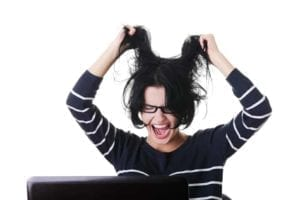 Frustrated woman screaming and pulling her hair because her spouse won't sign divorce papers