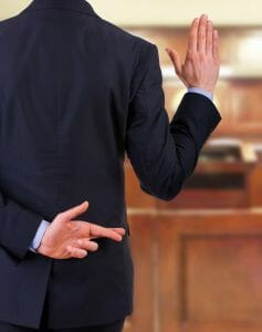 Man in court swearing to tell the truth while having his fingers crossed behind his back - lying in court