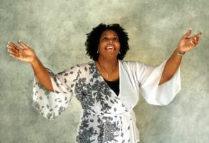 Grateful, smiling African American woman reaching her hands to the sky