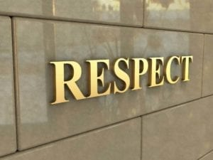 "Gold letters spell ""Respect"" on the wall of a building"