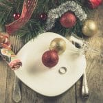 Christmas divorce shown by decorations on an empty dinner plate with a wedding ring on it