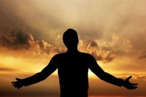Silhouette of a grateful man at sunrise.