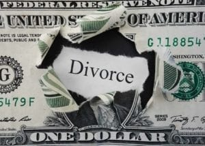 Hole ripped in a dollar bill with Divorce text. Can you afford to divorce?