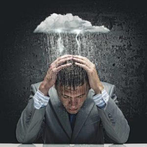 "Young businessman holding his head and thinking, ""divorce sucks!,""while a small cloud rains on him."