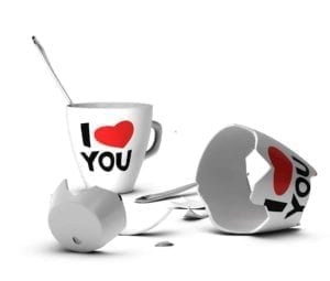 "Two white cups with ""I love you"" on them. One is shattered, signifying domestic violence"