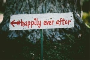 "Wooden sign with an arrow pointing to ""happily ever after."""