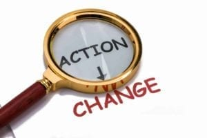 Magnifying Glass over the word action with an arrow to change: Should you act to change attorneys during divorce?