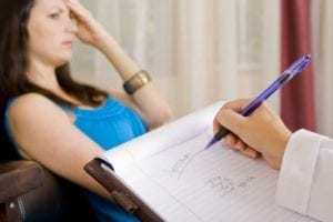 Close up of a therapists hand taking notes while a troubled woman rests on a couch in front of her. Counseling.