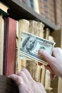Close up of hand putting $100s in a shelf of books, hiding money