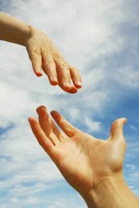 one hand reaching down to another in front of a blue sky. Lending a helping hand.