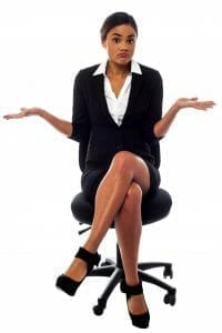 "Young professional woman sitting in an office chair with her hands up as if to say, ""I don't know."""
