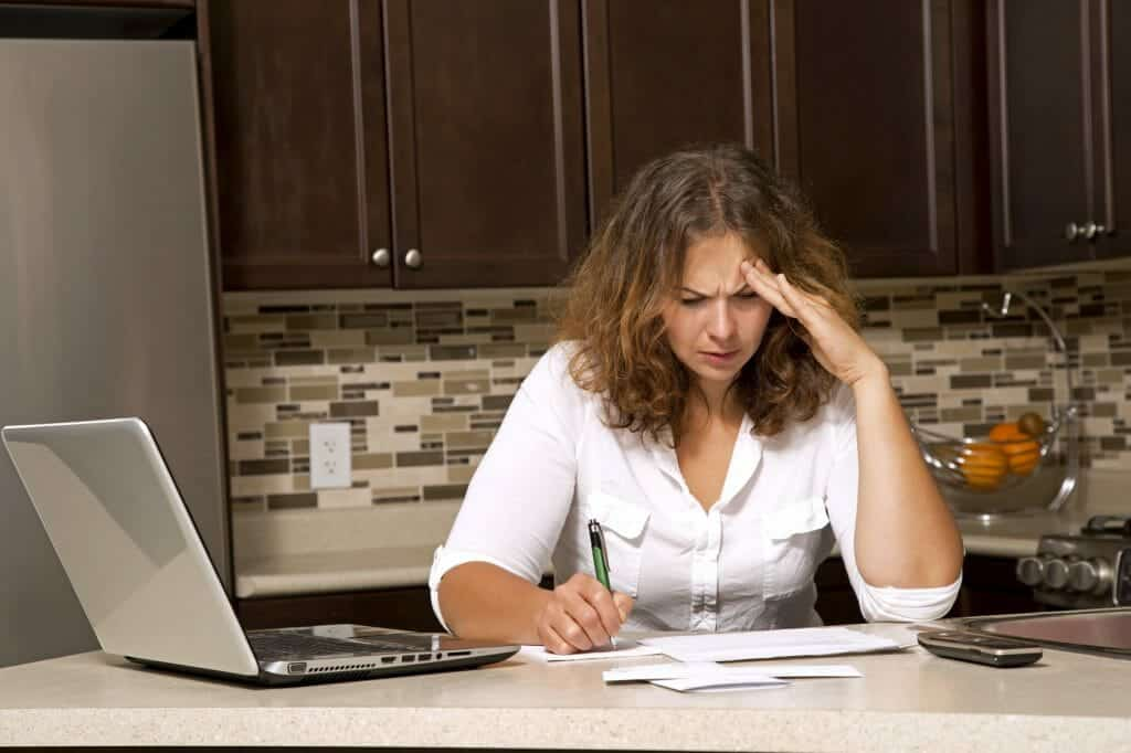 stressed woman looking at bills while sitting in the kitchen needs divorce financial planning