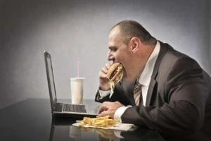 Obese man in front of laptop eating a hamburger and fries.