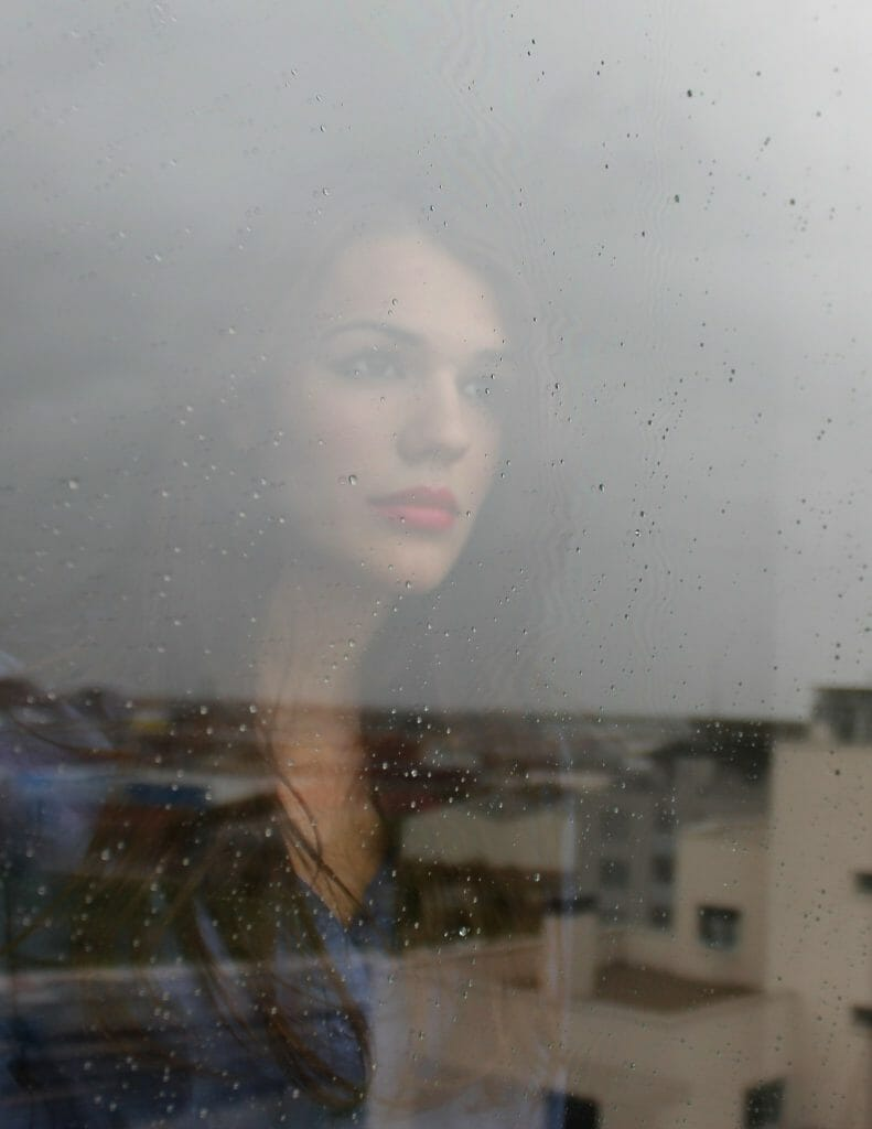 Beautiful woman in a bad marriage staring out through a rainy window