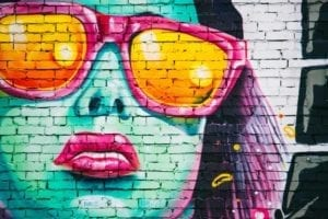 painting on a brick wall of a woman wearing rose colored glasses