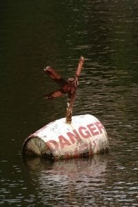"Old barrel with the word ""Danger"" floating in water signifying the danger of divorce without a lawyer"