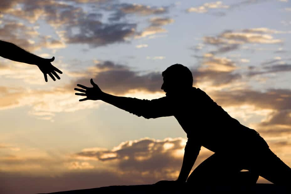 Silhouette of a hand reaching out to help a man get up. Divorce Counseling and Support concept.