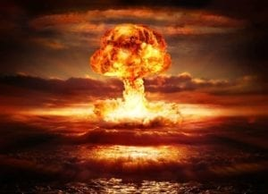 Explosion. Burning orange mushroom cloud over the ocean.