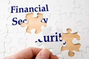 "Hand holding a piece to complete puzzle with the words ""financial security"""