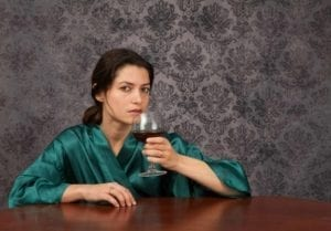 Woman looking at camera while drinking too much wine.