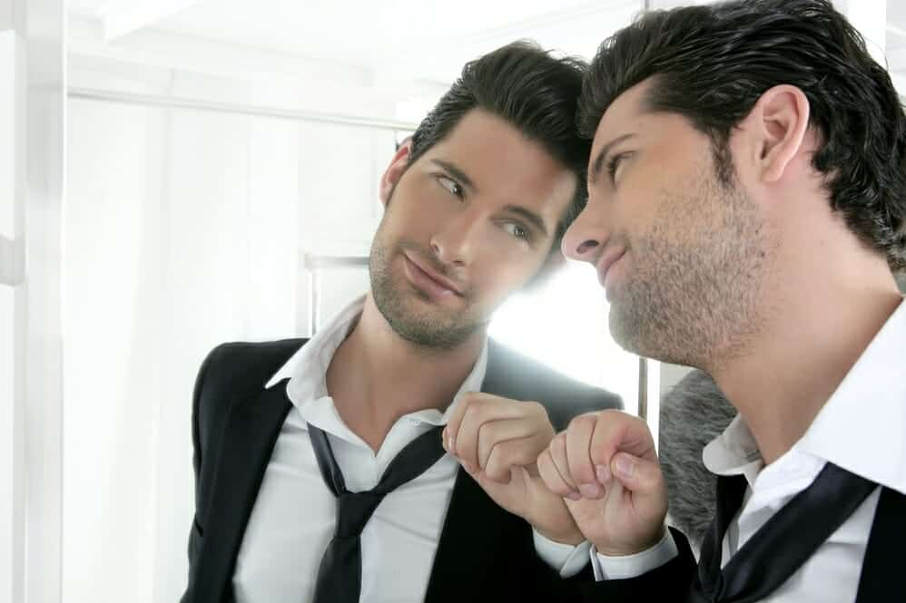 Good-looking narcissist man looking lovingly at his reflection in the mirror.