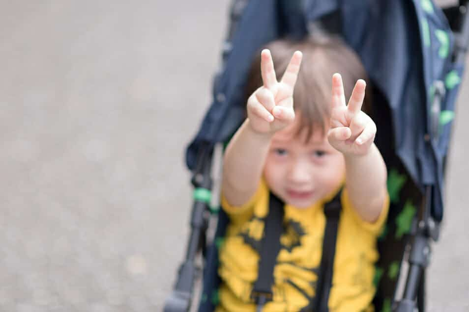 Child in stroller holding up peace signs with both hands, signifying peaceful divorce