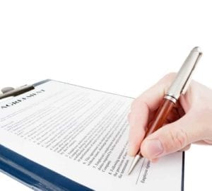 Close up of a hand signing a document.